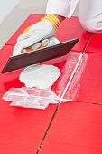 stock photo of grout  - Worker with rubber trowel applying white grout on red tile diagonally - JPG