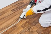 Worker Applies Silicone Sealant Spaces Of Old Wooden Floor