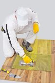 Worker Applies Tile Adhesive On Wooden Floor With Reinforcement Mesh