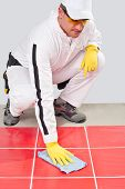 stock photo of grout  - Worker with yellow gloves blue towel clean red tiles grout - JPG