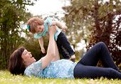 Mother in third trimester playing with daughter in park