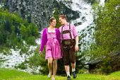 Happy Couple in traditional dress is walking in the meadow with mountain panorama