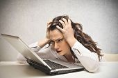 stock photo of collapse  - stressed businesswoman looks laptop - JPG
