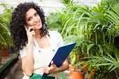 foto of greenhouse  - Female clerk talking on the phone in a greenhouse - JPG