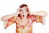 Mujer sorprendida que sostiene sus dedos alrededor de los ojos