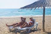 Young Couple Sunbathe In Longue On Sea Beach Under Sunshade