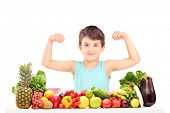 Healthy child showing his muscles and sitting on a table full of pile of food isolated on white background