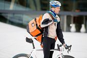 Young male cyclist in protective gear riding bicycle with a courier delivery bag
