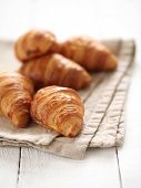stock photo of continental food  - Fresh homemade french croissants on a linen tablecloth - JPG