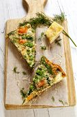 Wedges of vegetable frittata on a board, with parmesan and dill.