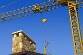 picture of entrepreneurship  - Yellow crane and blue sky on building site with roof and chimney - JPG