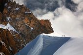 Team of two alpinists climbing a mountain