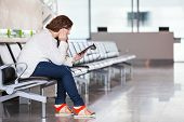 Tired Caucasian Woman With Devices Sitting In Airport Lounge