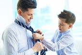 Photo of little boy helping his father tie necktie