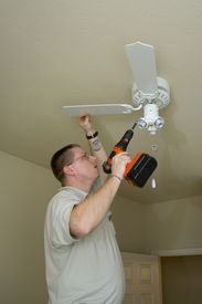 stock photo of light fixture  - Electrician installing new light fixture and fan combination - JPG