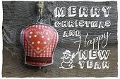 stock photo of elm  - Merry Christmas message handmade decoration gingham heart pattern on tin bell over rustic Elm wood background  - JPG