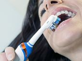 brunette woman brushing teeth with an electric toothbrush