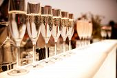 stock photo of buffet  - Row of glasses with champagne on the table