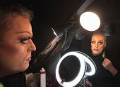 picture of drag-queen  - Serious drag queen in front of mirror with lamp - JPG