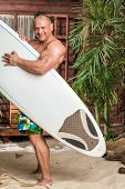 Smiling muscular man on a sandy beach with a surfboard near the wooden house