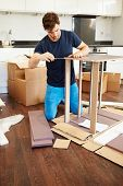Man Putting Together Self Assembly Furniture In New Home