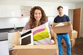 Couple Moving Into New Home And Unpacking Boxes