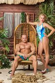 Beautiful girl in high-heeled shoes and muscular man on the sandy beach with wooden chair