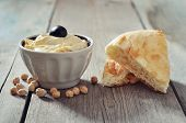 stock photo of fresh slice bread  - Bowl of fresh hummus with olive and bread slices on wooden background - JPG