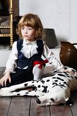 Serious pretty little boy in medieval costume sits with dalmatian near fireplace.