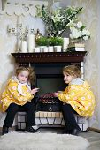 Two little girls in same clothes sits near fireplace and wicker rocking chair and warm hands in cosy room. Focus on right girl.