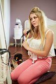 Teenage Girl Straightening Hair In Bedroom
