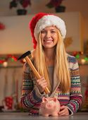 Portrait Of Smiling Teenage Girl In Santa Hat With Hammer And Pi