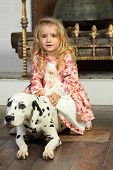 Happy pretty little girl in medieval costume sits with dalmatian near fireplace.