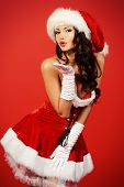 Attractive young woman in Santa Claus costume over red background. Christmas.