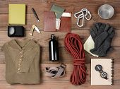 Overhead view of gear laid out for a backpacking trip on a rustic wood floor. Items include, rope, g