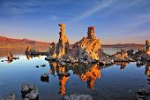 The magic of Mono Lake. Outliers - bizarre calcareous tufa formation on the smooth water of the lake. Orange sunset