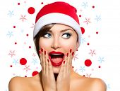 Christmas Woman. Beauty Model Girl in Santa Hat isolated on White Background. Funny Laughing Surprised Woman Portrait. Open Mouth. True Emotions. Red Lips and Manicure. Beautiful Holiday Makeup.