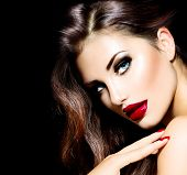 Sexy Beauty Girl with Red Lips and Nails. Provocative Make up. Luxury Woman with Blue Eyes. Fashion Brunette Portrait isolated on black background. Gorgeous Woman Face. Long Hair