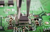 pic of microchips  - Mounting microchip on green electronic circuit board with tweezers - JPG