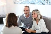 stock photo of meeting  - Senior couple meeting financial adviser for investment - JPG
