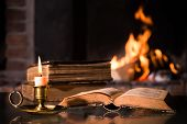 stock photo of candle flame  - An open Bible with a burning candle in front of fireplace - JPG