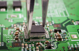 stock photo of microchips  - Mounting microchip on green electronic circuit board with tweezers - JPG