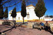 Men sitting on bench by church, Colmenar.