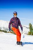 Man in ski mask standing on the snowboard
