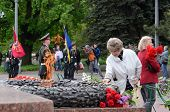 Old lady put flowers to Eternal Flame in commemoration of Soviet soldiers,Odessa,Ukraine