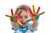 picture of child development  - Boy with hands painted in colorful paints ready to make hand prints - JPG