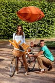 Young And Joyful Couple Having Fun In The Park With Bicycle And Airship On It