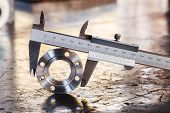 stock photo of vernier-caliper  - Close up vernier caliper measure diameter of stainless steel flange - JPG