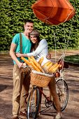 Young And Joyful Couple Hugging In The Park With Bicycle And Airship On It