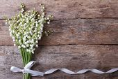 stock photo of lily  - Beautiful floral frame with lilies of the valley flowers on old wooden table - JPG